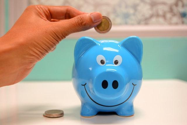 човек държащ монета над прасенце касичка