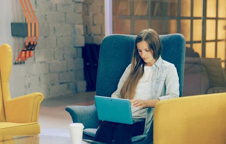 момиче стои с лаптоп Леново на колене