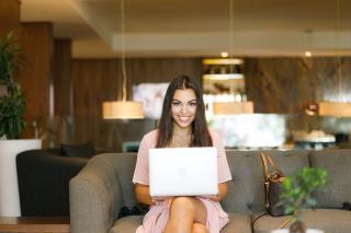 усмихната жена седяща на диван с лаптоп в ръце